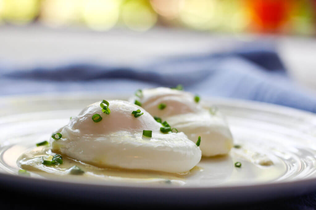 These Perfectly Poached Eggs with Dijon Sauce are easy and delicious.  Plus- you'll learn how to poach eggs without vinegar, swirling the egg, or using kitchen gadgets!