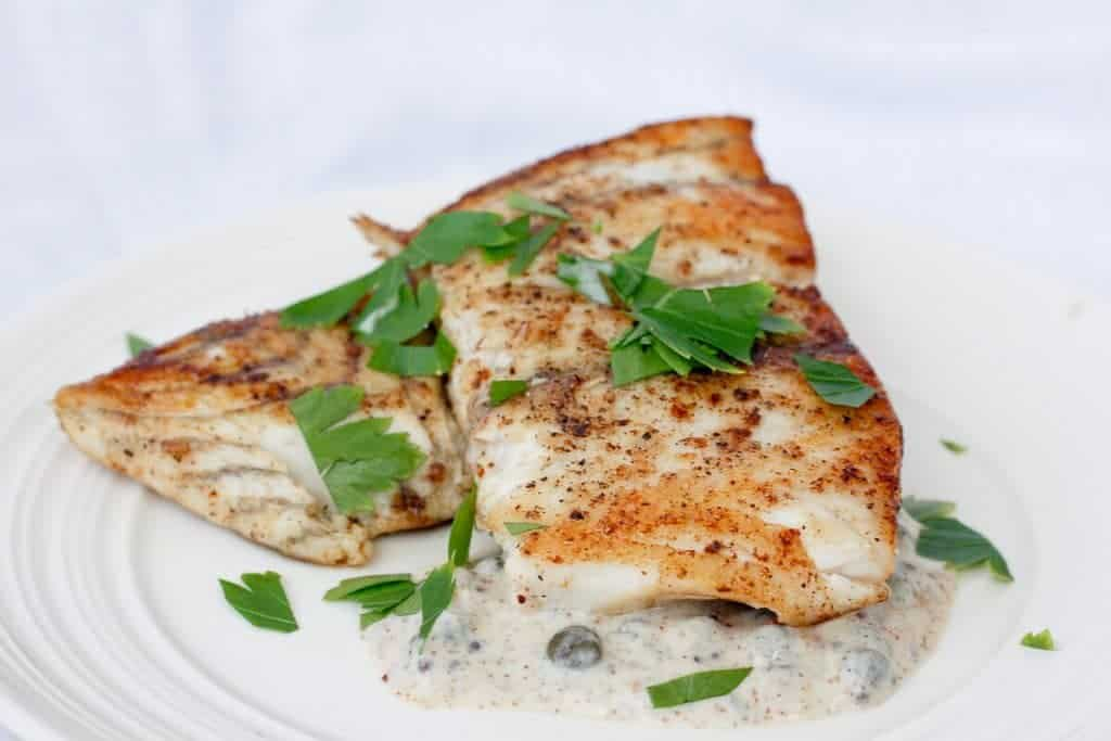 This Seared Barramundi (Asian Sea Bass) is cooked to perfection in browned butter, and served with a tangy Mustard Caper Sauce. This flavorful dish is ready in under 20 minutes, and is perfect for Date Night! champagne-tastes.com