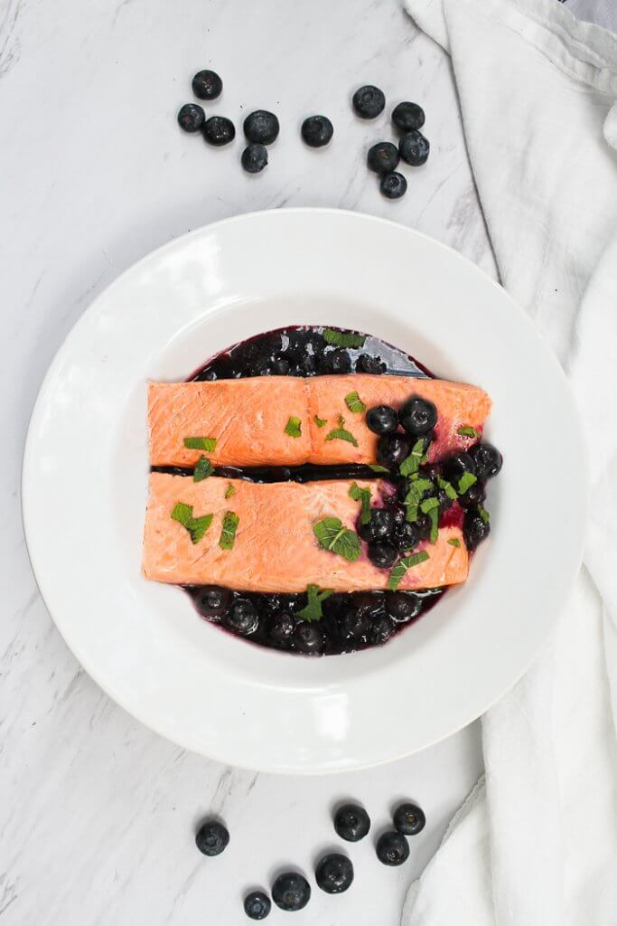 This Poached Salmon with Blueberry Sauce is made with decadent king salmon poached in spiced white wine, and served with an easy blueberry sauce. champagne-tastes.com #ad