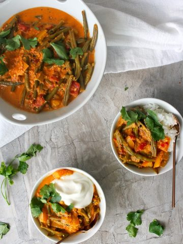 Vegetable korma in serving dishes with yogurt and with rice
