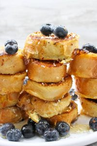 This Coconut French Toast is made with thick, dense bread, crusted with coconut, smothered in fruit, and drizzled with honey.