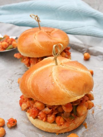Two vegan sloppy joes with tomato chickpea mixture spilling out of challah buns. Sandwiches are on a countertop with a blue cloth in the back.