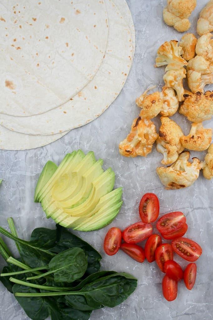 Veggie wrap ingredients- buffalo cauliflower, tomatoes, avocado, spinach, and tortillas