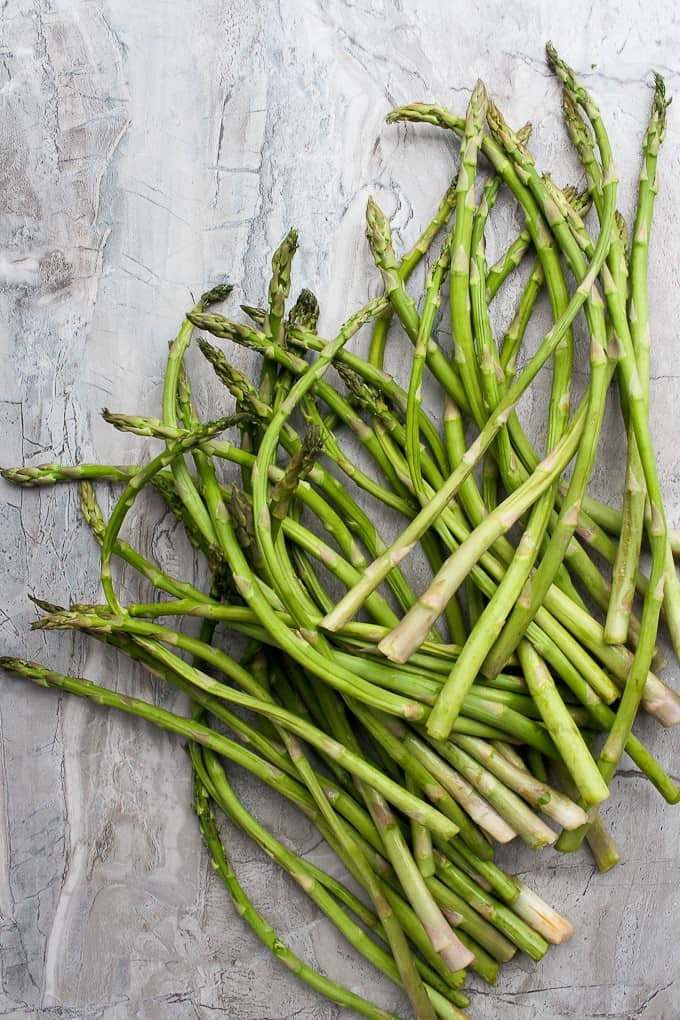 A bunch of asparagus scattered on the counter