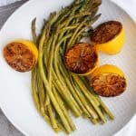 Oven-roasted asparagus and charred lemons on a plate