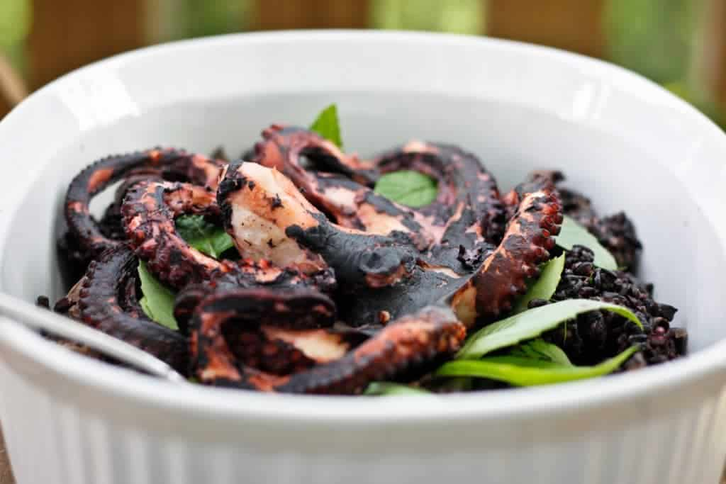 Grilled octopus in a serving dish with black rice