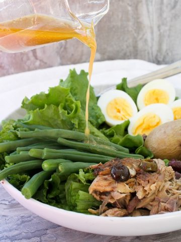 Pouring vinaigrette on the Mackerel Nicoise Salad