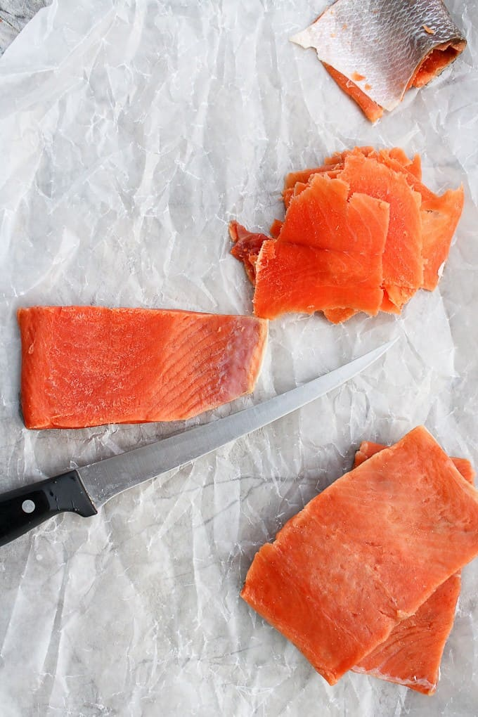 cutting the cured salmon on a white counter