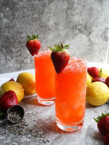 strawberry lemonade in glasses with lavender petals, strawberries, and lemons