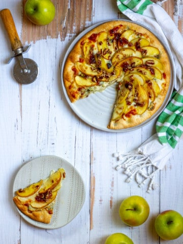 apple gorgonzola pizza with a slice cut out