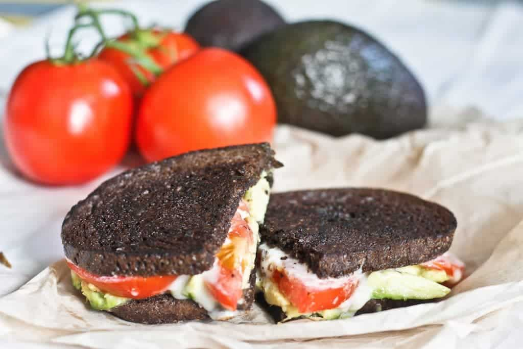 Washed rind stinky cheese, tomato, avocado grilled in pumpernickel bread, with tomatoes and avocado in the background