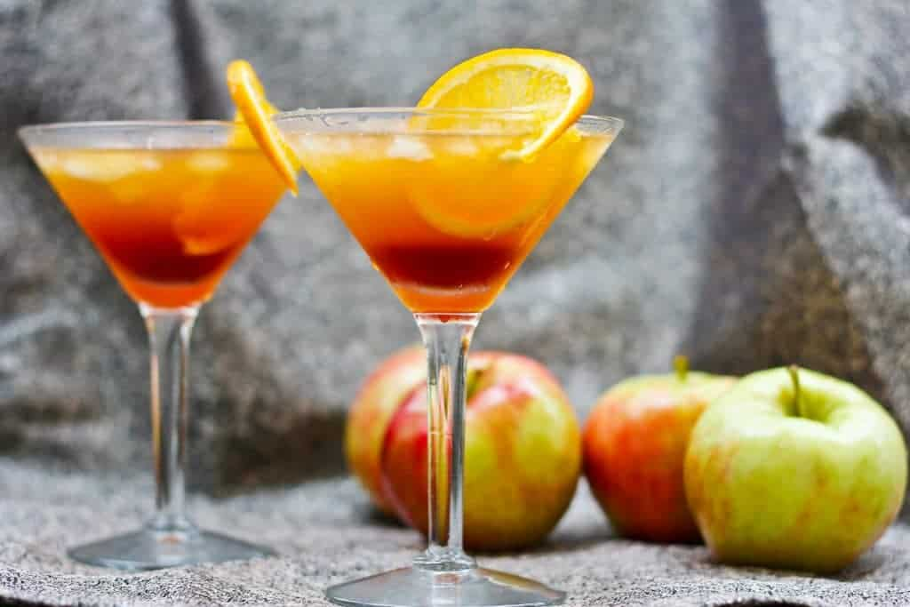 Apple Cider Kentucky Sunrise in a Martini Glass with an Orange on the Rim