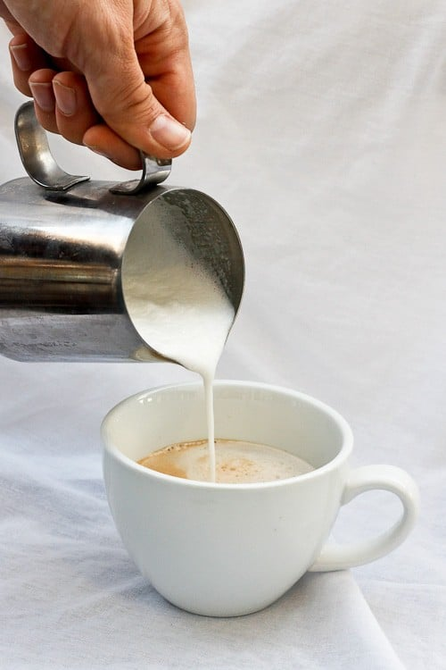 Pouring frothed eggnog into the espresso