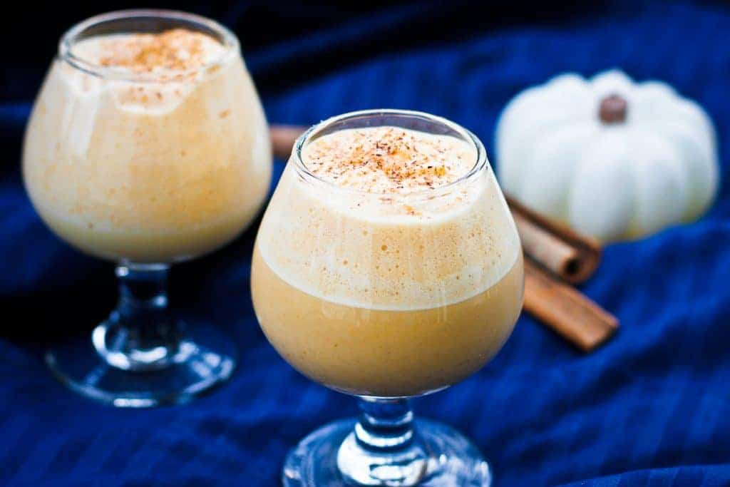 Pumpkin Eggnog in Small Glasses with Cinnamon Sticks and a Small White Pumpkin in the Background