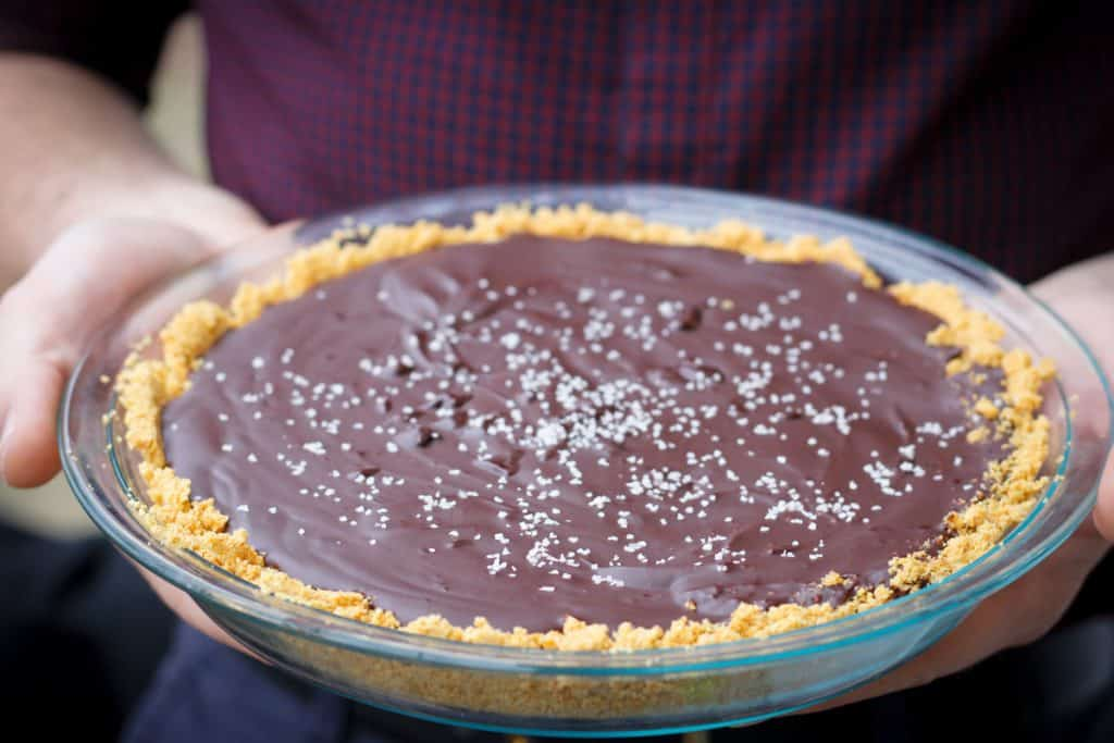 man holding a salted bourbon chocolate pie