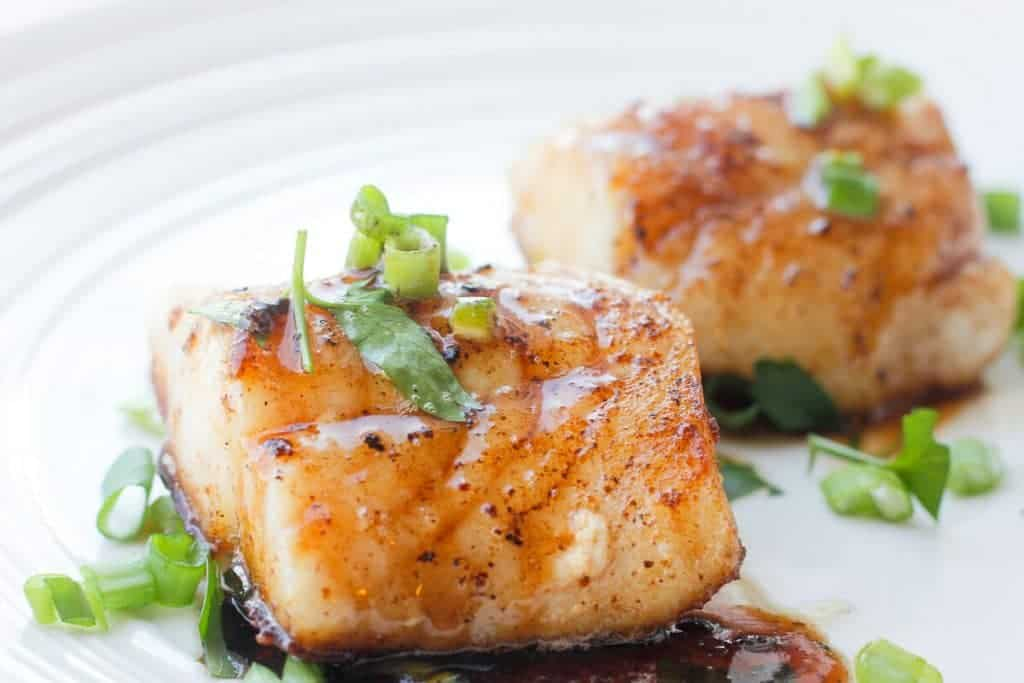 Two pan-seared cod fillets on a plate, covered with bourbon sauce and topped with green onion