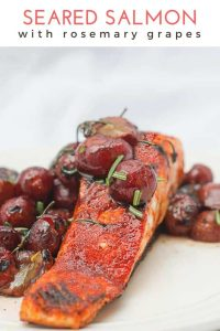 This easy gluten free recipe for Seared Salmon with Rosemary Grapes cooked in olive oil in a hot cast iron pan for a fine dining dinner experience. #Seafood #Salmon #Seared #Grapes