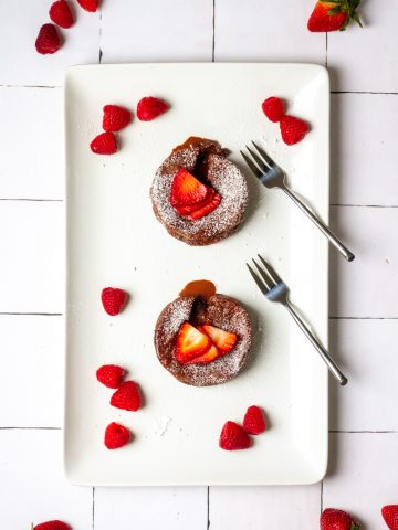 two chocolate lava cakes on a serving platter with berries