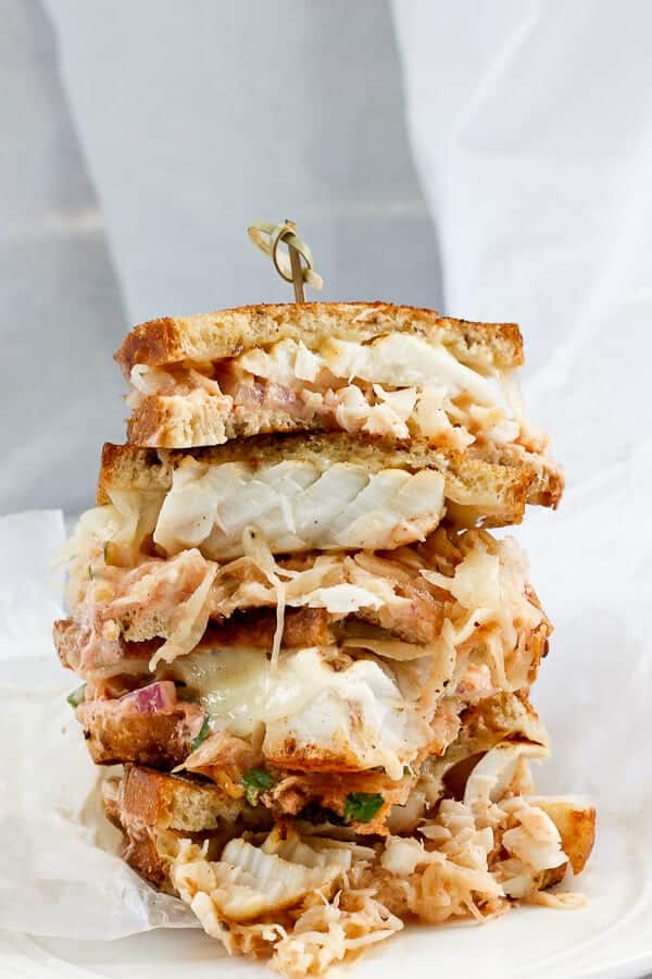 This Cod Reuben Sandwich is a fishy take on a classic deli-style reuben, and is piled high with seared cod, sauerkraut, and a homemade yogurt-based Russian dressing.