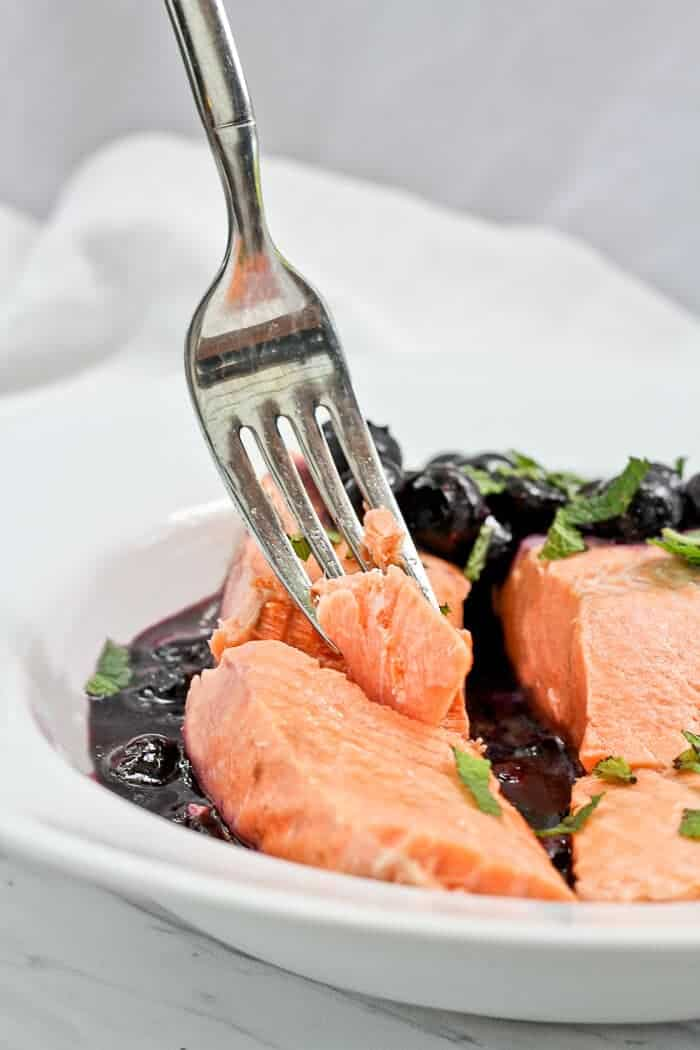 Flaking Apart Poached Salmon inside the Serving Dish