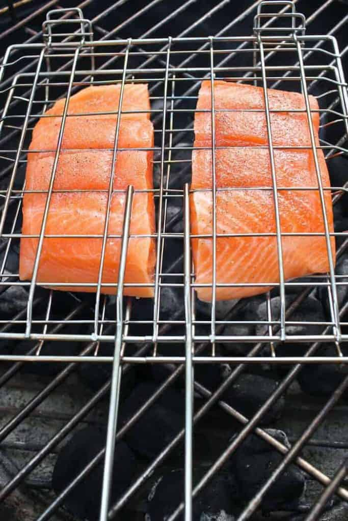 Two King Salmon Fillets in a Fish Basket over a Charcoal Grill