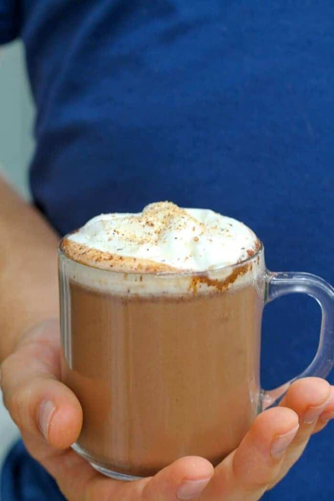 Holding Pumpkin Spice Hot Chocolate in a see-through mug with whipped cream on top.