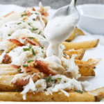 Learn how to make crab fries! These baked fries are loaded with cheese, garlic yogurt sauce, green onions or chives, and are an easy seafood appetizer or game day side dish.