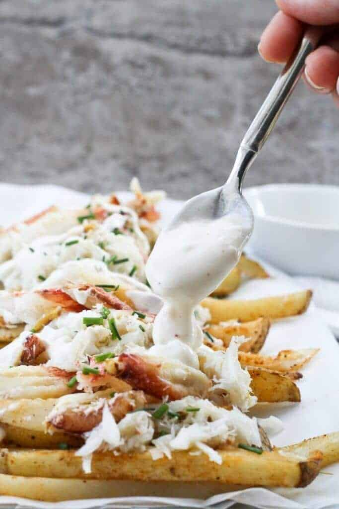 Drizzling yogurt sauce over top of fries