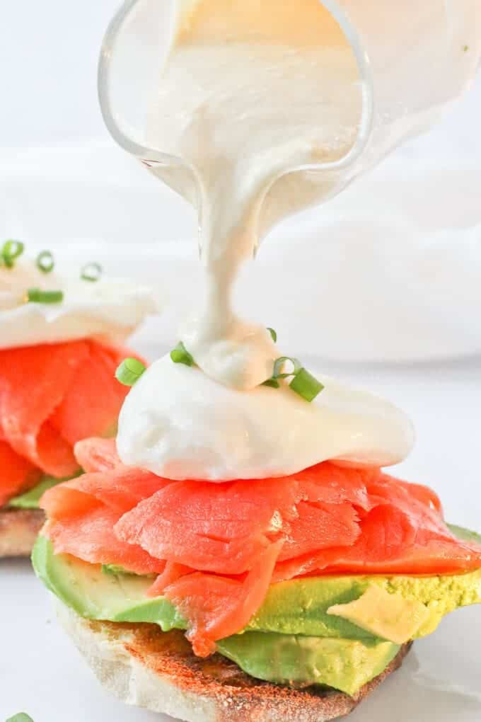 Pouring sauce on Healthy Smoked Salmon Eggs Benedict