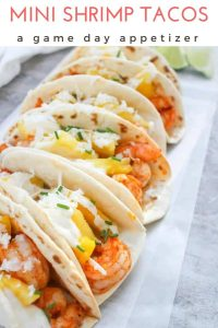 These mini shrimp and pineapple tacos are a healthy game day appetizer, or a perfect tapas small plate. Top them with spicy shrimp, pineapple, and a quick and easy yogurt sauce!