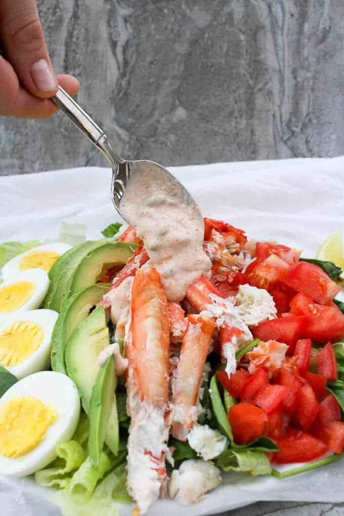 Pouring Yogurt Dressing on a Crab Louie Salad