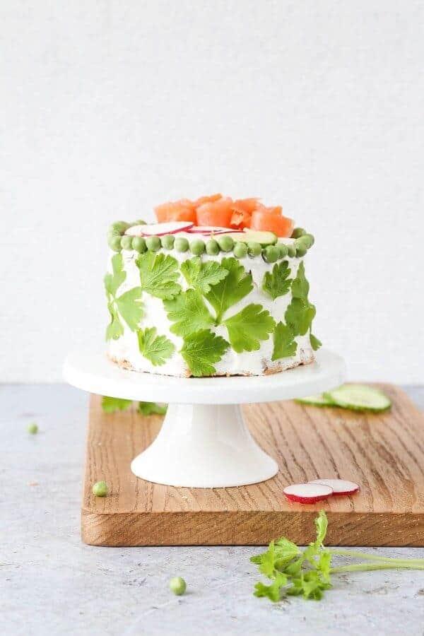 {Cold-Smoked Salmon} Swedish Smörgåstårta Sandwich Cake on a white cake stand- from Little Sunny Kitchen