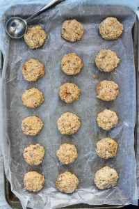 Unbaked sardine fish cakes on a baking sheet with a scoop.