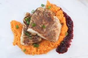Two cod fillets stacked on top of sweet potato mash, with puréed raisin sauce on the side.