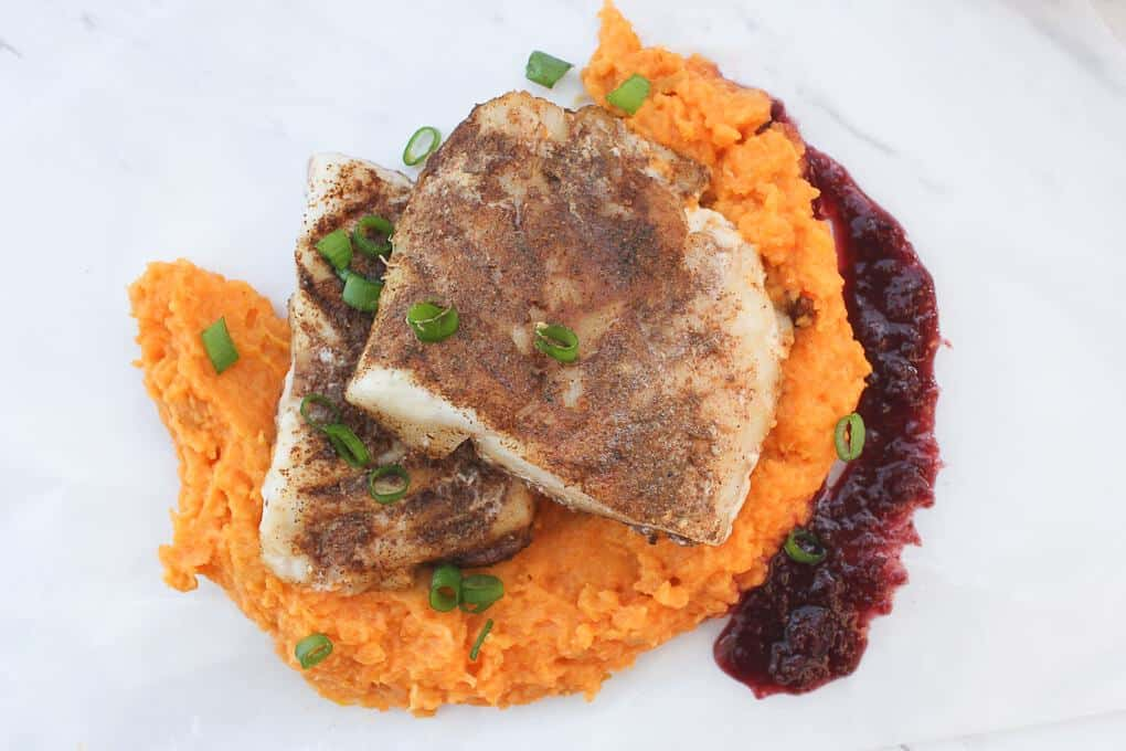 Two spiced fish fillets stacked on top of sweet potato mash, with puréed raisin sauce on the side.
