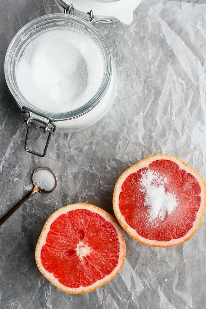 Sprinkling sugar onto a halved grapefruit