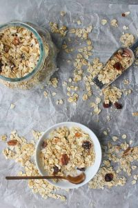 Muesli in a cereal bowl with milk, in a glass jar, and in a scoop