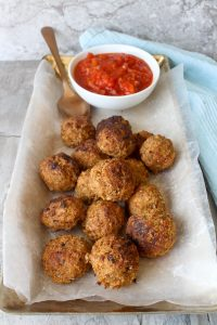 Albondigas de pescado (fish balls / fish meatballs) on a serving tray with tomato sauce