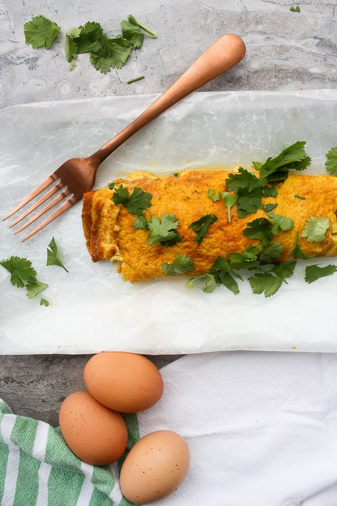 Masala Omelette with eggs and cilantro on the counter