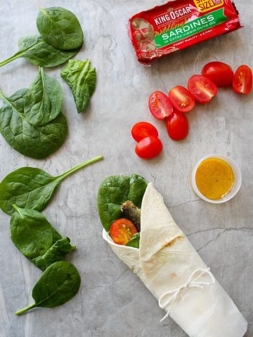 Fish wraps with sardines, tomatoes, dressing, and spinach on a countertop