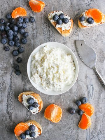 Homemade ricotta / cottage cheese in a bowl with crostini and fruit