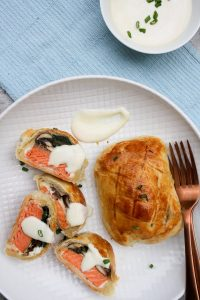 Salmon Wellington and yogurt sauce on a serving platter