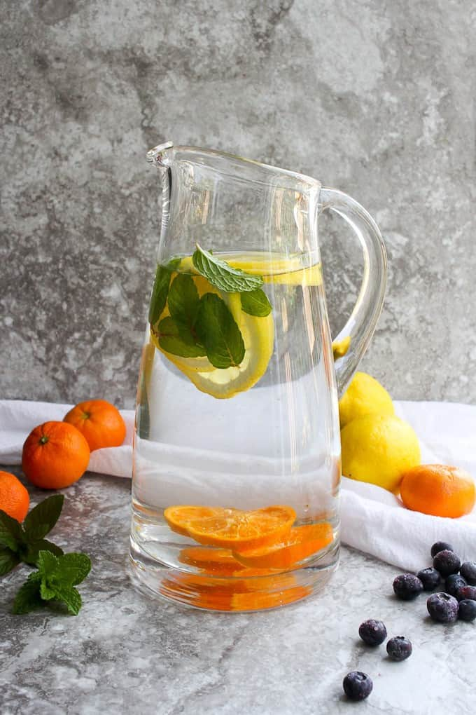 Infused water in pitcher with fruit and citrus on the side