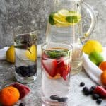 Infused water in pitcher and glasses with fruit and citrus on the side