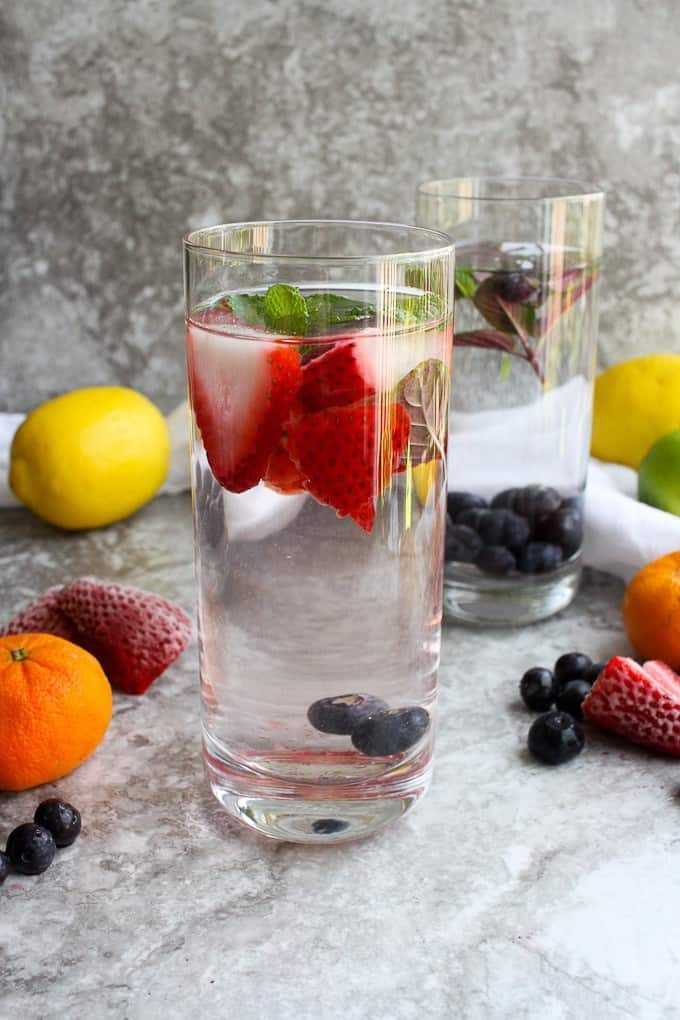Infused water in glasses with fruit and citrus on the side