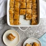 cooked baklava in a serving dish and plates