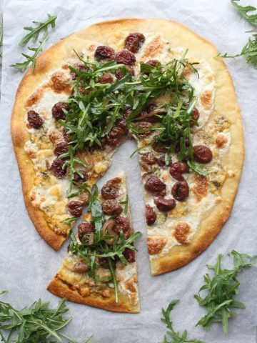 Arugula pizza with one slice cut out and extra arugula