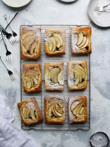 apple tarts on a cooling rack surrounded by forks and plates