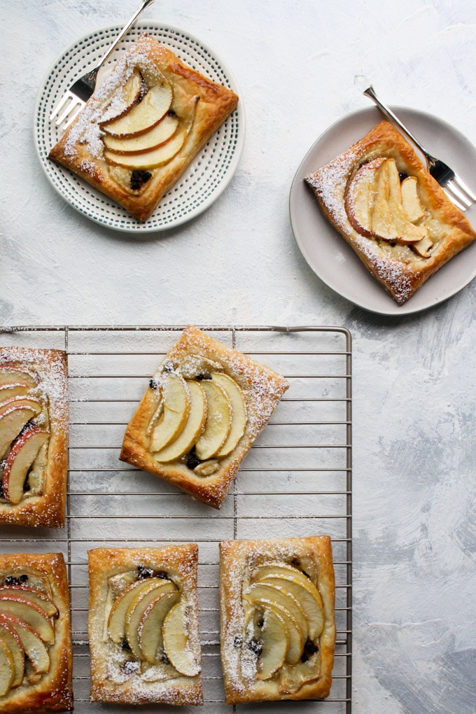 apple tarts on a cooling rack, two on plates