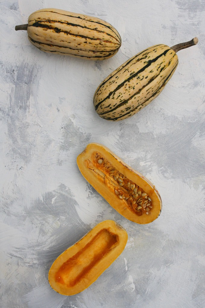 delicata squash, two whole, one cut open